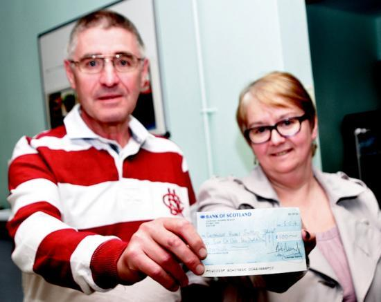 Photograph of Bob is on the other side of the camera for charity cheque presentation